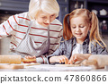 Smiling grandmother and granddaughter making cookies and looking glad 47860866