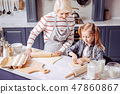 Friendly grandmother looking at her granddaughter while making cookies with her 47860867
