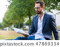 Serious businessman reading book in the park 47869334