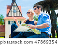 Close-up of young couple holding map 47869354