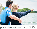 Rear view of couple looking at lake 47869358