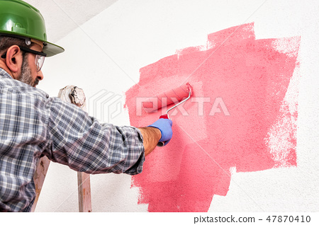 House painter at work painting the wall 47870410
