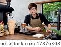 Asian entrepreneur barista sitting at counter  47876308