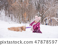 Little girl, dog catch ring toy and play together 47878597