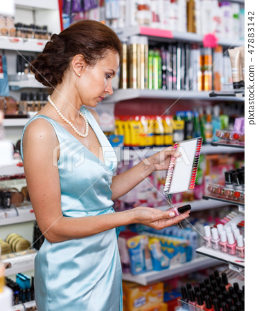 Woman with schemes choosing new nail polish in cosmetics store 47883142