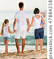 Man and woman with children standing with back to camera on beach 47884238