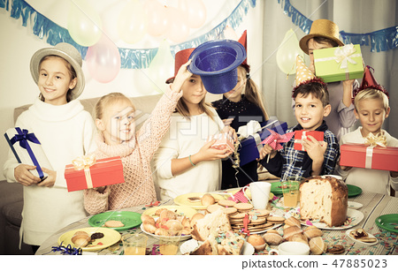 Children exchanging presents at party 47885023