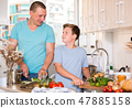Boy and his father are cooking soup together in the kitchen 47885158
