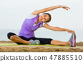 Woman practising yoga poses sitting on beach by sea 47885510