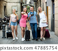 Four happy traveling persons walking in city 47885754