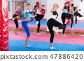 women are boxing and doing kick with coach 47886420