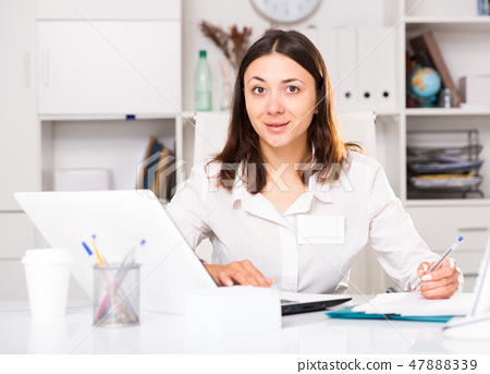 Young woman working with laptop and papers at the office 47888339