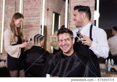Hairdresser man doing styling of guy with electric hair clipper 47890554