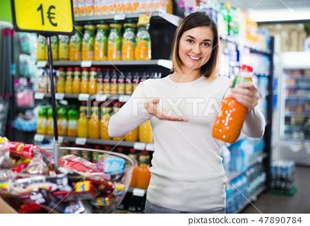 Woman choosing refreshing beverages in supermarket 47890784