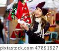 Woman choosing Christmas decoration at market 47891927