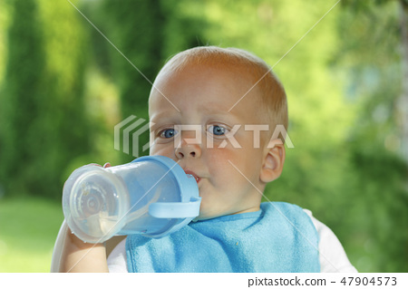Funny toddler is drinking water from a bottle. It stands on a green lawn 47904573