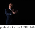 Portrait of handsome man in a suit pointing a gun  47906146