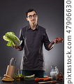 Man preparing delicious salad with tomatoes and cabbage on a gray background. 47906630