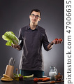 Man preparing delicious salad with tomatoes and cabbage on a gray background. 47906635