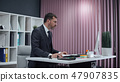 Businessman working in office, standing work at computer. 47907835