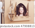 Little princess in crown play with her cardboard castle. True emotion of happiness of the child. 47908813