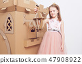 Little princess in crown play with her cardboard castle. True emotion of happiness of the child. 47908922