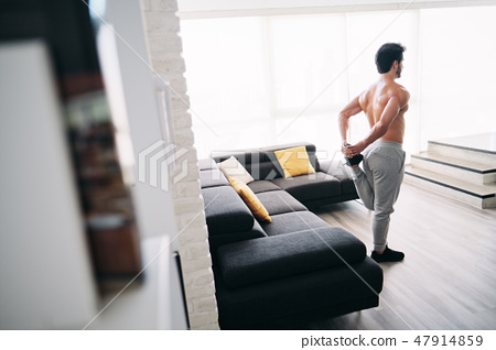 Adult Man Fitness Training At Home Stretching Muscles Before Workout 47914859