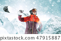 Female skier standing with skies in one hand on background mountain landscape 47915887