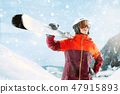 Female skier standing with skies in one hand on background mountain landscape 47915893