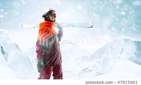 Female skier standing with skies in one hand on background mountain landscape 47915901