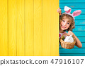 Child playing with Easter bunny 47916107