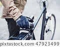 A midsection of a cyclist with electrobike standing outdoors in town. 47923499