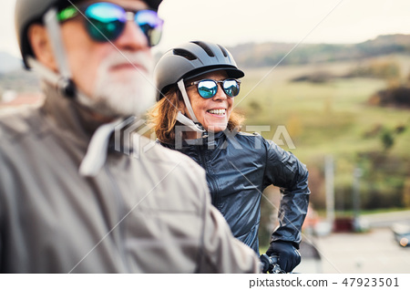 Active senior couple with electrobikes standing outdoors on a road in nature. 47923501