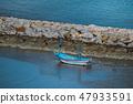 Small blue boat, stone dam and sea  47933591
