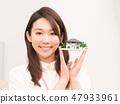 有一個微笑的建築模型的一名婦女 47933961