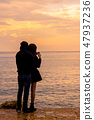 a couple looks at the sea at sunset 47937236