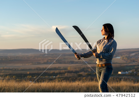 Girl on a high mountain trains with a machete 47942512