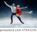 Professional man and woman figure skaters performing on ice show 47943245