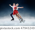 Professional man and woman figure skaters performing on ice show 47943249