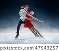Professional man and woman figure skaters performing on ice show 47943257