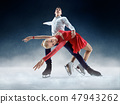 Professional man and woman figure skaters performing on ice show 47943262