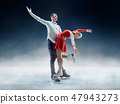 Professional man and woman figure skaters performing on ice show 47943273