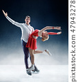 Professional man and woman figure skaters performing on ice show 47943278