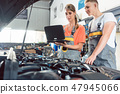 Female auto mechanic checking the engine error codes 47945066