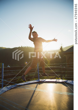 Cute funny cheerful young kid jumping outdoors 47946946