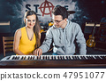 Piano teacher giving music lessons to his student 47951077