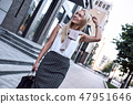 Attractive young woman walking outdoors 47951646