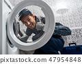 Glad of own results. Working man plumber in bathroom checking washing mashine 47954848