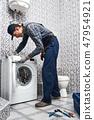 Checking washing machine work. Working man plumber in bathroom 47954921