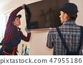 Setting plasma television. Two technician installing television in kitchen 47955186
